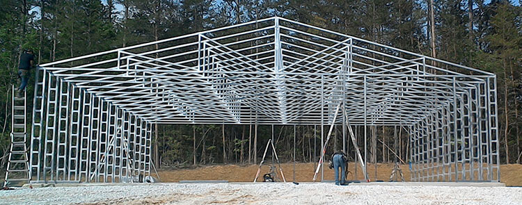 A worker erects the trusses of a 60-foot-wide metal building
