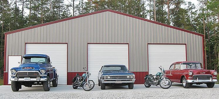 Two cars, a truck, and two motorcycles sit in front of a 60-by-100 large steel building with red-and-tan siding and three 14-foot garage doors
