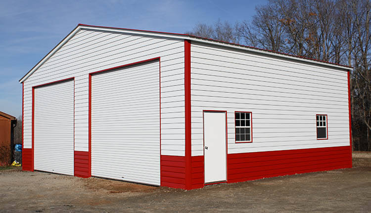 A red-and-white large metal garage with lap siding