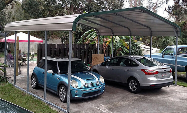 A metal carport protects two vehicles from the elements